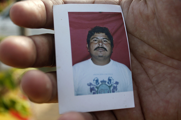 A relative holds a photo of Gregorio Jiménez de la Cruz in February 2014, shortly after the journalist was kidnapped in front of his daughters. Jiménez was later murdered and his body mutilated. (AP/Viridiana Zepeda)
