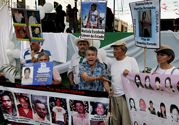 Images of victims from drug cartels and gangs in Oaxaca are held up at a rally in 2011. The state is home to a thriving drug trafficking operation that has driven up the murder rate. (AP/Eduardo Verdugo)