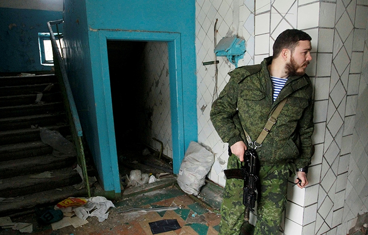 A pro-Russian separatist inspects a building damaged in fighting with Ukrainian security forces in Donetsk, eastern Ukraine, on February 23, 2017. (Reuters/Alexander Ermochenko)