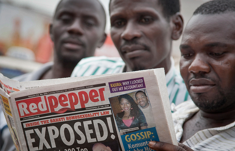 Ugandans read a copy of the newspaper Red Pepper in Kampala, in this February 25, 2014, file photo. (AP/Rebecca Vassie)