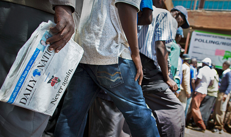 """A Kenyan voter in Nairobi carries a copy of the Daily Nation newspaper as he waits to vote in the March 4, 2013, elections. The headline, """"Never Again,"""" refers to the post-election violence of 2007. (AP/Mackenzie Knowles-Coursin)"""