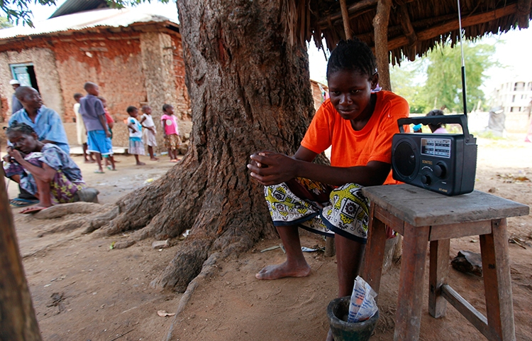 A young Kenyan listens to the news on the radio in this March 2013 file photo (Reuters/Joseph Okanga)