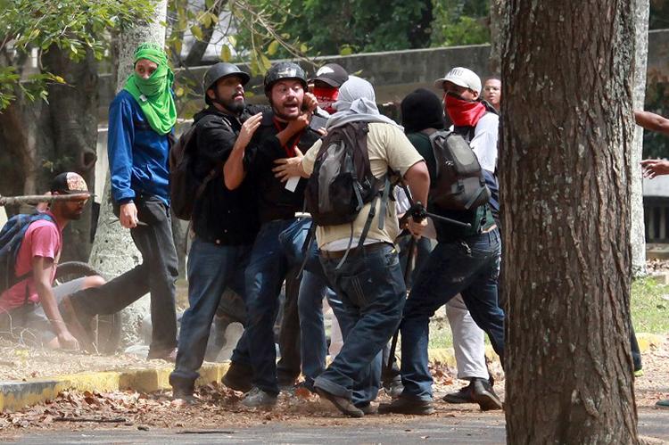 Miembros de un 'colectivo', un grupo armado progubernamental, agreden a Leonardo Rodríguez (centro), un reportero gráfico con el diario El Nacional, mientras cubría a una manifestación de estudiantes en la Universidad Central de Venezuela (UCV) en Caracas, el 3 de abril de 2014. (AFP/Federico Parra)