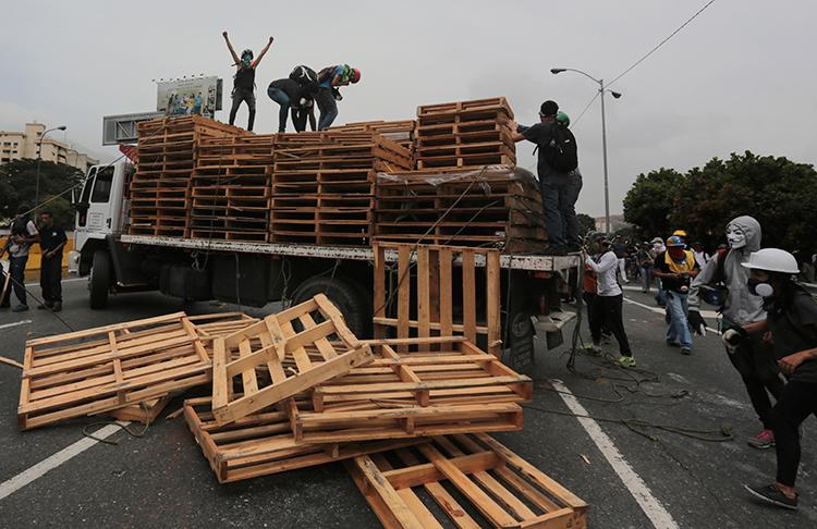 Manifestantes descargan tarimas de madera de un camión al que obligaron a parar en una autopista en Caracas, el 22 de mayo de 2017. (AP/Fernando Llano)