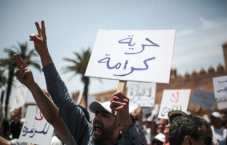 """A protester in Rabat holds a sign saying """"Freedom and Dignity,"""" June 11, 2017. (AP/Mosa'ab Elshamy)"""