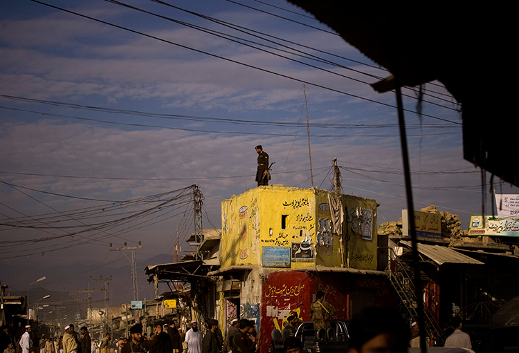 In this November 29, 2008, file photo, a member of the Frontier Corps paramilitary group surveys a street in Khar, Pakistan. (AP/Emilio Morenatti)