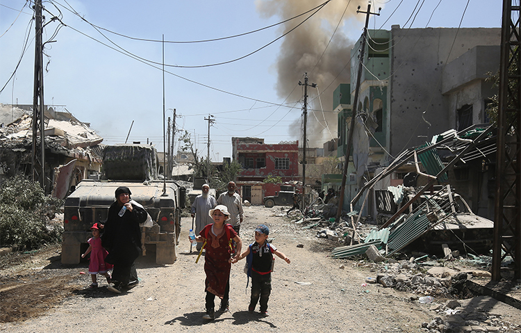 Iraqis flee their Mosul homes during fighting in May. Local journalists say they went into hiding to survive during the takeover by Islamic State militants. (AFP/Ahmad Al-Rubaye)