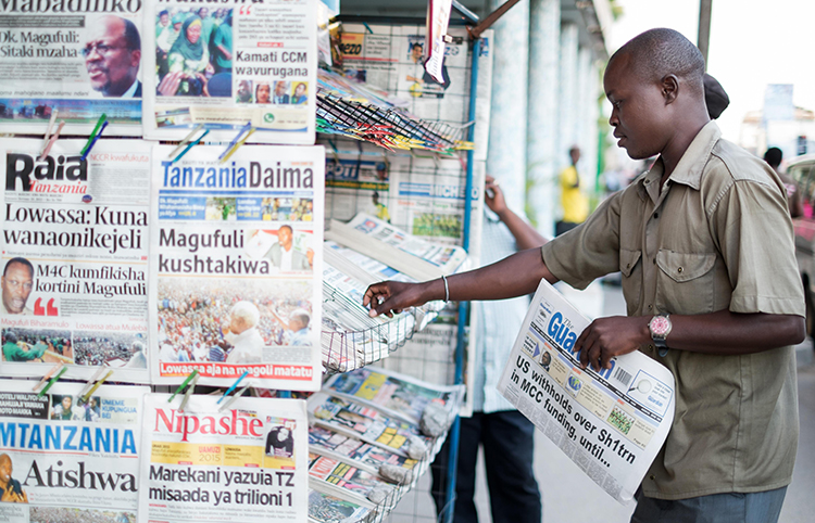 A newspaper vendor straightens papers at his stand in Tanzania in September 2015. The country's Information Minister has imposed a 24-month ban on the weekly, Mawio. (AFP/Daniel Hayduk)