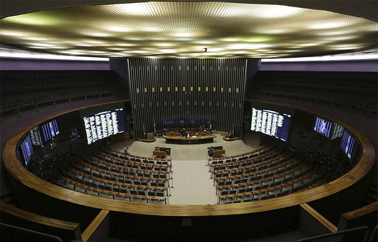 A Câmara dos Deputados do Brasil realiza uma sessão em 12 de abril com apenas dois deputados depois que o Supremo Tribunal Federal anunciou investigações de corrupção envolvendo vários políticos. Um jornalista perguntou por que o tribunal divulgou detalhes de seu telefonema com uma fonte, apesar de ele não fazer parte da investigação. (AP / Eraldo Peres)