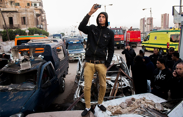 An Egyptian uses his phone to record the aftermath of a deadly explosion outside a police headquarters in December 2013. Journalists who use smartphones and messaging apps in their reporting say they are wary of surveillance and trolling under Egypt's press crackdown continues. (AP/Ahmed Ashraf)