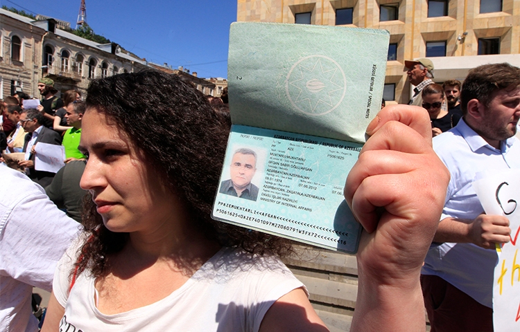 Leyla Mustafayeva holds her husband's passport at a May 29 rally in Tbilisi to protest the detention of Afgan Mukhtarli, who was abducted and forcibly taken to Azerbaijan. (AP/Shakh Aivazov)