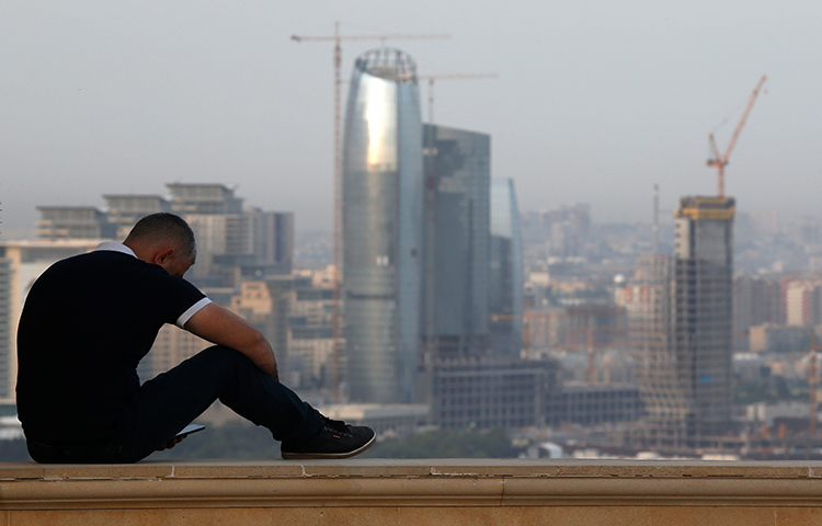 A man sits on a parapet in Baku in June 2016. A court in the Azerbaijani capital sentenced a journalist to seven years in jail. (Reuters/Maxim Shemetov)