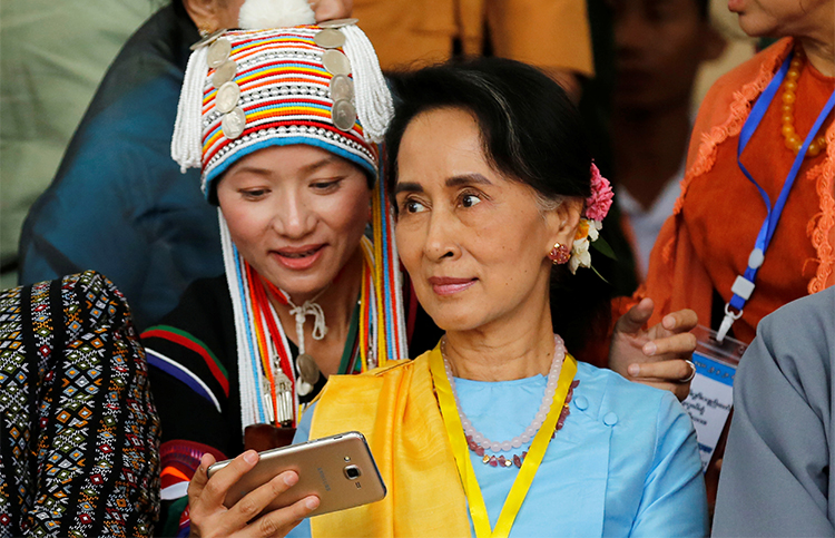 A woman takes a selfie with Myanmar State Counsellor Aung San Suu Kyi in Myanmar in May. Journalists say conditions for press freedom have not significantly improved under her rule. (Reuters/Soe Zeya Tun)