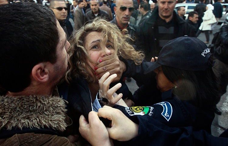 In this file photograph, police detain a protester during a March 6, 2014, demonstration in Algiers against Algerian President Abdulaziz Bouteflika's decision to run for a fourth term. (Reuters/Ramzi Boudina)