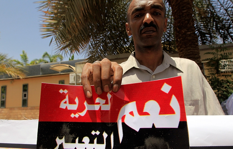 """A Sudanese journalist in Khartoum holds a sign reading """"Yes to freedom of expression"""" in this file photo from June 2012. (Reuters/Mohamed Nureldin Abdallah)"""