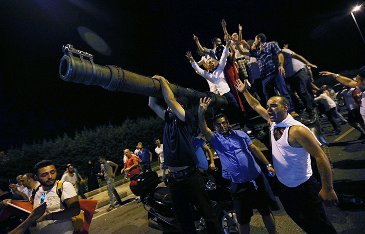 People stand atop a military tank at Istanbul's Ataturk Airport, in the early hours of July 16, 2016. (Reuters/Huseyin Aldemir)
