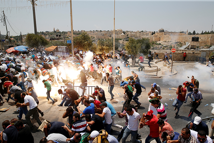 Palestinians run from tear gas and sound grenades at a July 21, 2017, protest outside Jerusalem's old city. (Reuters/Ammar Awad)