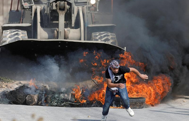 A Palestinian protester runs from Israeli military machinery in the West Bank village of Khobar, near Ramallah, July 22, 2017. (Reuters/Mohamad Torokman)
