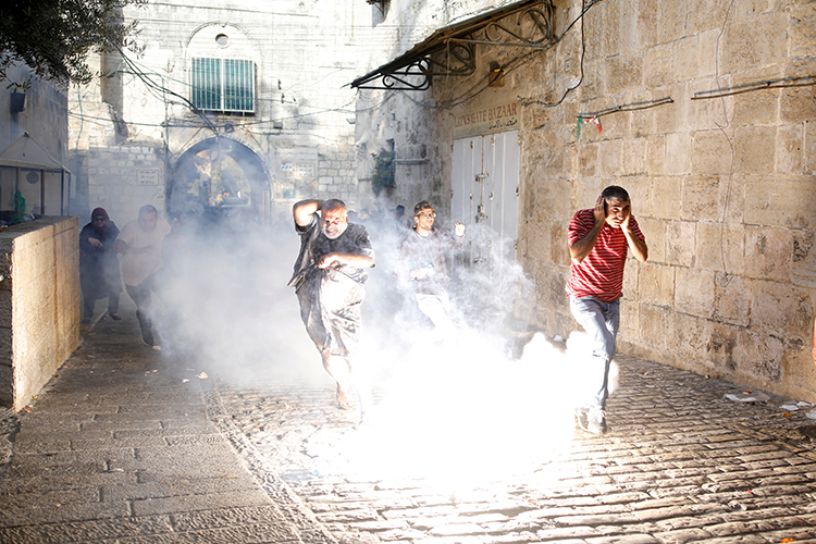 Palestinians run from tear gas and stun grenades in the old city of Jerusalem, July 27, 2017. (Reuters/Amir Cohen)