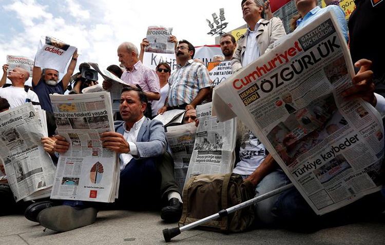 Journalists and press freedom advocates read Cumhuriyet newspaper at a protest demanding the release of 17 employees and directors of the newspaper outside their trial in Istanbul, July 28, 2017. (Reuters/Murad Sezer)