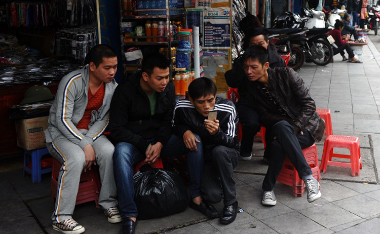 In this December 5, 2014, file photo, men read the news on a mobile phone in central Hanoi. (AFP/Hoang Dinh Nam)