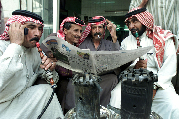 In this 2001 file photo, Jordanian men read a newspaper in a cafe in Amman. (Reuters/Ali Jarekji)