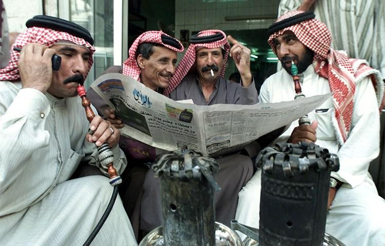 In this 2001 file photo, Jordanian men read a newspaper in a cafe in Amman. (Reuters/Ali Jarekji)