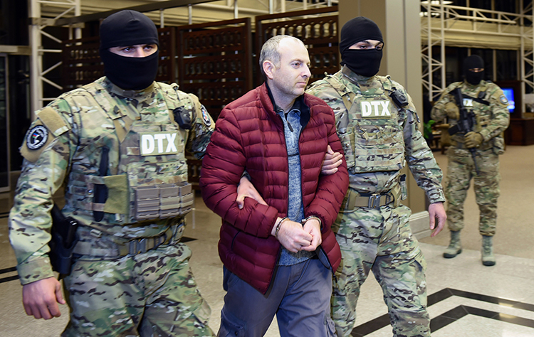 Aleksandr Lapshin is escorted through Baku airport in February after being extradited from Belarus. An Azerbaijan court has jailed the blogger for three years. (AFP/Tofik Babayev)