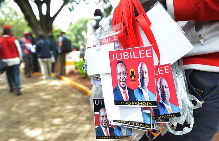 A vendor sells badges of Kenya's President Uhuru Kenyatta, left, and his deputy William Ruto in May. Kenya is seeking to restrict commentary on social media ahead of the August elections. (AFP/Simon Maina)