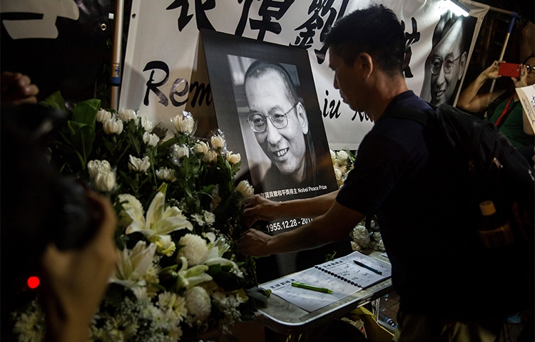 Supporters pay their respects to Chinese Noble laureate Liu Xiaobo at a vigil outside the Chinese Liaison Office of Hong Kong. The jailed activist and journalist died in July. (AFP/Isaac Lawrence)