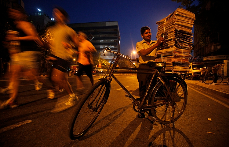 A newspaper vendor stacks newspapers on his bicycle in Mumbai. Indian journalists say companies are using the legal notices as an attempt to silence critical reporting. (AP/Rajesh Kumar Singh)