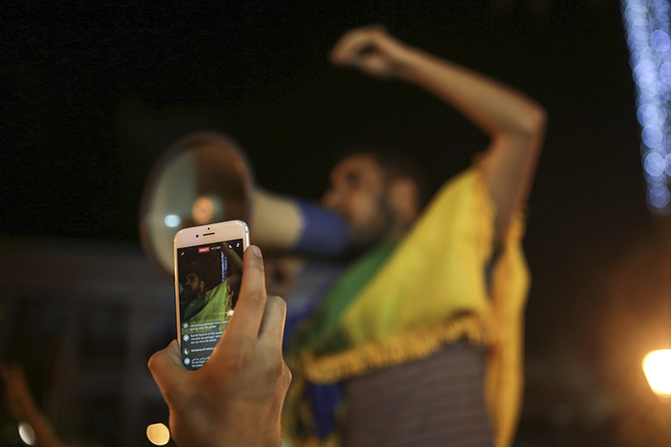 A man broadcasts via Facebook during a demonstration in Rabat in support of protests in the northern Rif region. Police arrested a journalist who was on his way to cover the protests in Rif. (AP Photo/Mosa'ab Elshamy)