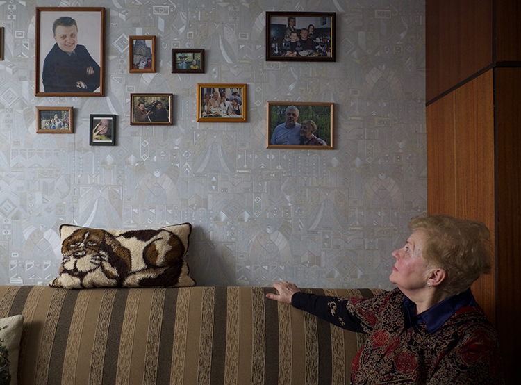 Lyudmila Sheremet, pictured looking at photos of her son in her Minsk apartment, says investigators have rarely provided her with updates into her son's murder investigation. (Christopher Miller)