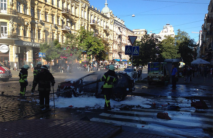 In this photograph taken by Olena Prytula before she realized her partner was in the explosion, firefighters douse the vehicle in a Kiev street. (Olena Prytula)