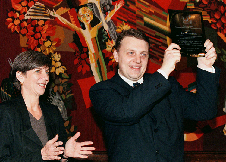 Pavel Sheremet, pictured with CPJ's then-executive director Ann Cooper, lifts his International Press Freedom Award during a ceremony in 1998. (Reuters/Vasily Fedosenko)