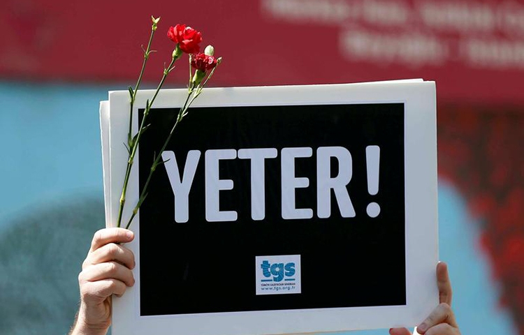 """A member of the Journalists Union of Turkey TGS holds a sign reading """"Enough"""" in a protest in Istanbul to mark World Press Freedom Day, May 3, 2017. (Reuters/Murad Sezer)"""