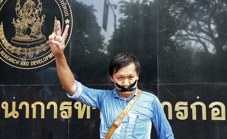 Pravit Rojanaphruk stands outside the Bangkok military base where he had been summoned on May 25, 2014. (AFP)