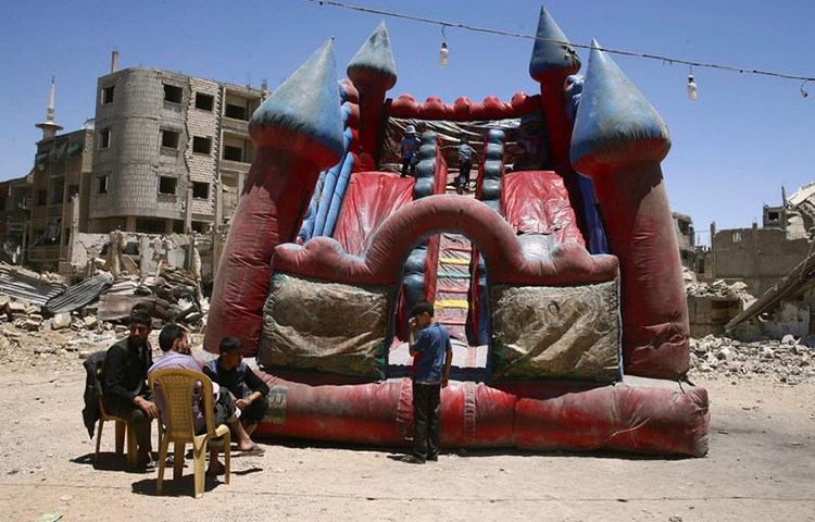 Children play in an inflatable castle in the rebel-held city of Douma, Syria, June 26, 2017. (Reuters/Bassem Khabieh)
