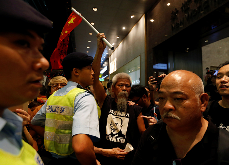 A protester carrying a defaced Chinese national flag is blocked by a police officer during a march to mourn the death of Nobel laureate Liu Xiaobo, in Hong Kong, July 15, 2017. A court in Dali, China, on August 3, 2017, sentenced journalist Lu Yuyu to four years in prison for his work documenting protests on social media. (Reuters/Bobby Yip)