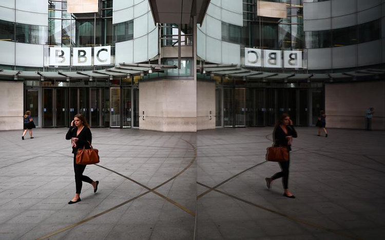 A woman is reflected as she passes the BBC's broadcasting house in London, July 19, 2017. (Reuters/Neil Hall)