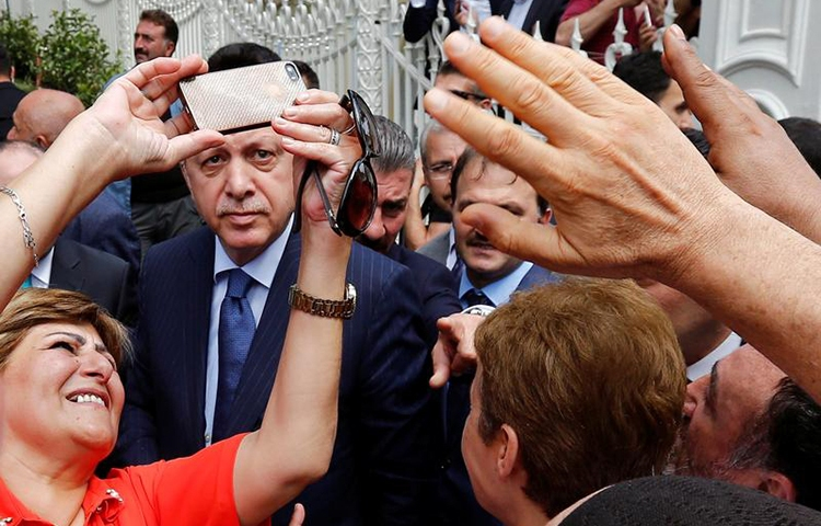 A woman takes a selfie with Turkish President Recep Tayyip Erdoğan in Istanbul, August 4, 2017. (Reuters/Murad Sezer)