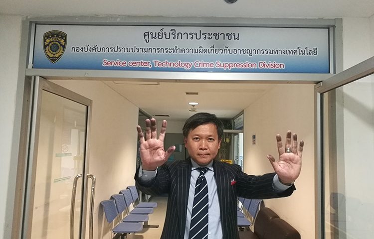 Thai columnist Pravit Rojanaphruk raises his hands, stained by ink from being fingerprinted, at the Royal Thai Police's Technology Crime Suppression Division in Bangkok, August 8, 2017. (Pravit Rojanaphruk)