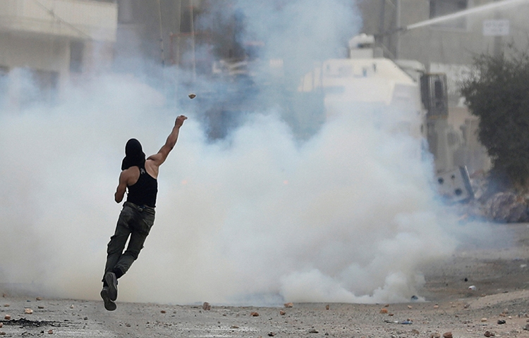 A Palestinian man hurls stones at Israeli soldiers in the West Bank village of Deir Abu Mashal, near Ramallah, August 10, 2017. Israeli and Palestinian security forces have increased repression of the media as political tensions have increased in recent weeks. (Reuters/Mohamad Torokman)