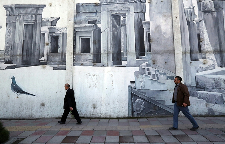 Iranians walk past street art in the southwestern district of Tehran in January 2016. Security agents arrested two journalists in the city in August (AFP/Atta Kenare)