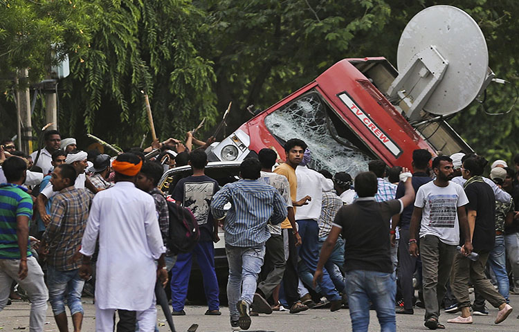 Sect members overturn a broadcasting van on the streets of Panchkula, India on August 25, 2017. Deadly riots have broken out in a north Indian town after a court convicted their guru of raping two of his followers.(AP Photo/Altaf Qadri)