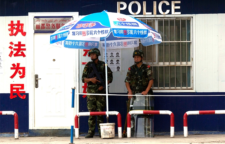 Chinese paramilitary policemen guard a checkpoint in China's Xinjiang province. Authorities briefly detained a Canadian journalist in the region who was interviewing residents about the Uighurs' security situation. (AP/Ng Han Guan, File)