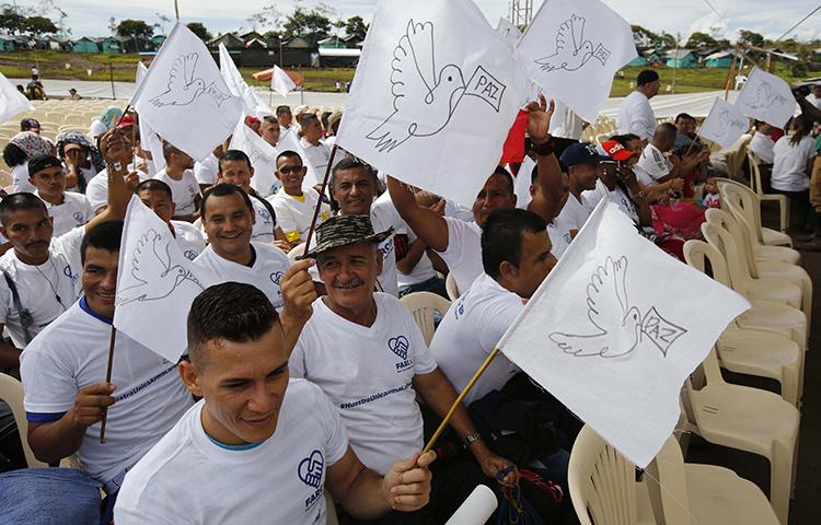 Os rebeldes das Forças Armadas Revolucionárias da Colômbia, FARC, agitam bandeiras de brancas pela paz durante um ato para comemorar a conclusão de seu processo de desarmamento em Buenavista, Colômbia, em 27 de junho de 2017. (AP/Fernando Vergara)