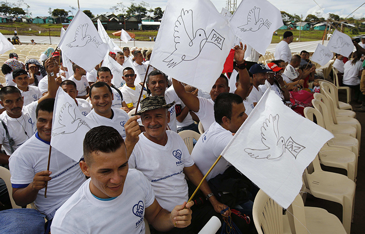 Rebels of the Revolutionary Armed Forces of Colombia, or FARC, wave white peace flags during an act to commemorate the completion of their disarmament process in Buenavista, Colombia, on June, 27, 2017. (AP/Fernando Vergara)