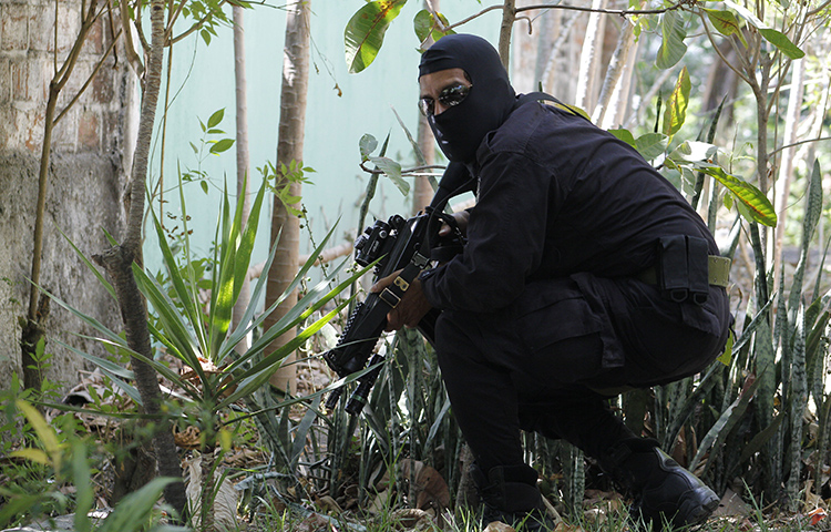 In this April 5, 2016 photo, a masked and armed policeman crouches as he patrols a gang controlled neighborhood in San Salvador, El Salvador. Journalists at two publications received threats on social media after one of the outlets published a story critical of security forces. (AP Photo/Alex Peña)