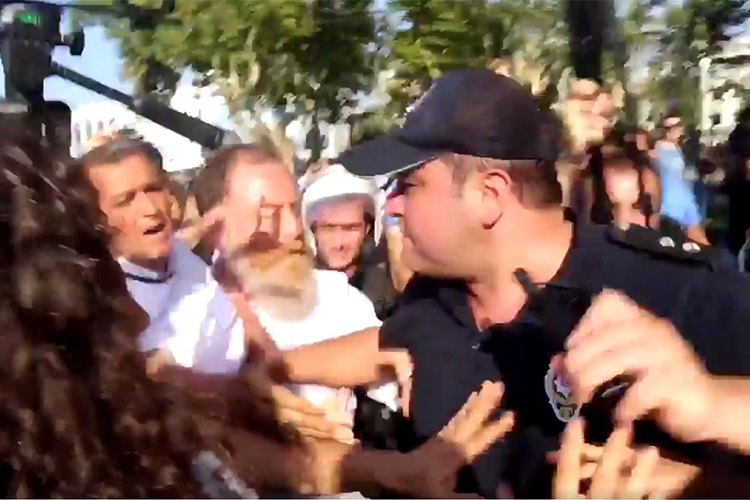 A screen shot of a Dihaber video shows a police officer scuffling with journalists at an August 6 opposition party protest in Istanbul.